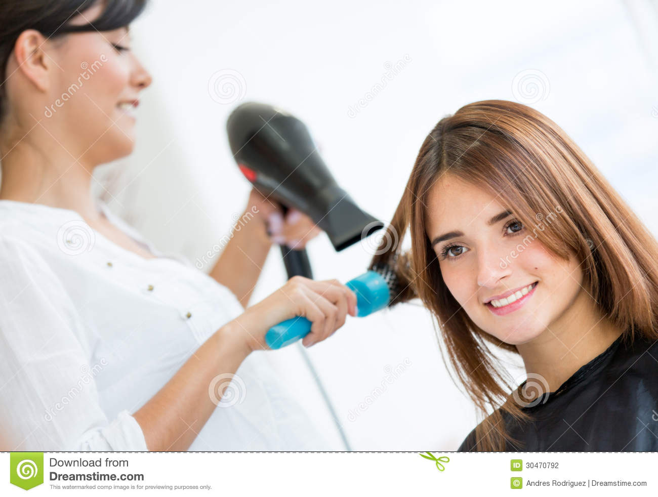 Beautiful women at the hair salon blow drying her hair.