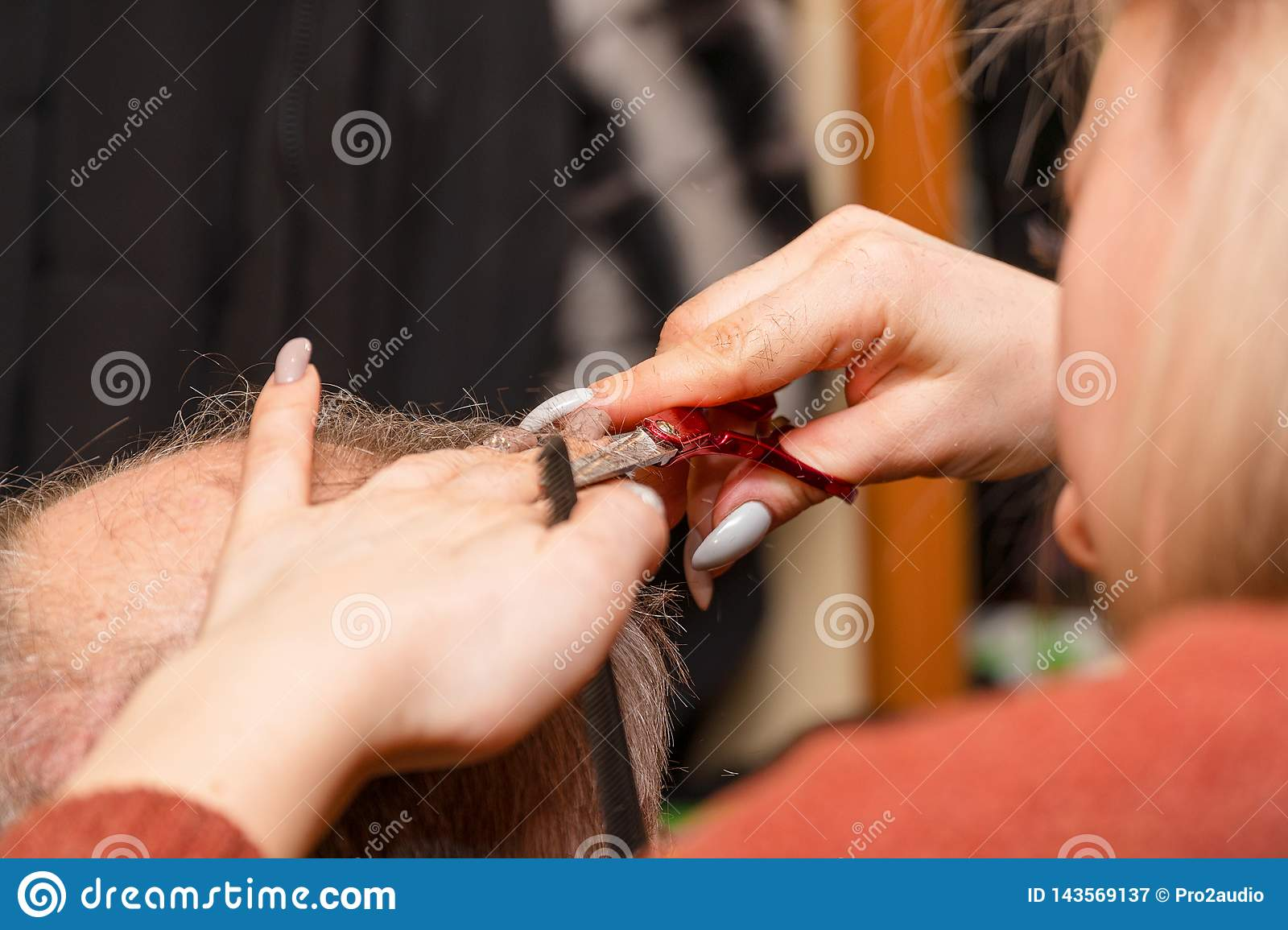 Woman hairdresser cuts a man with a receding hairline with scissors
