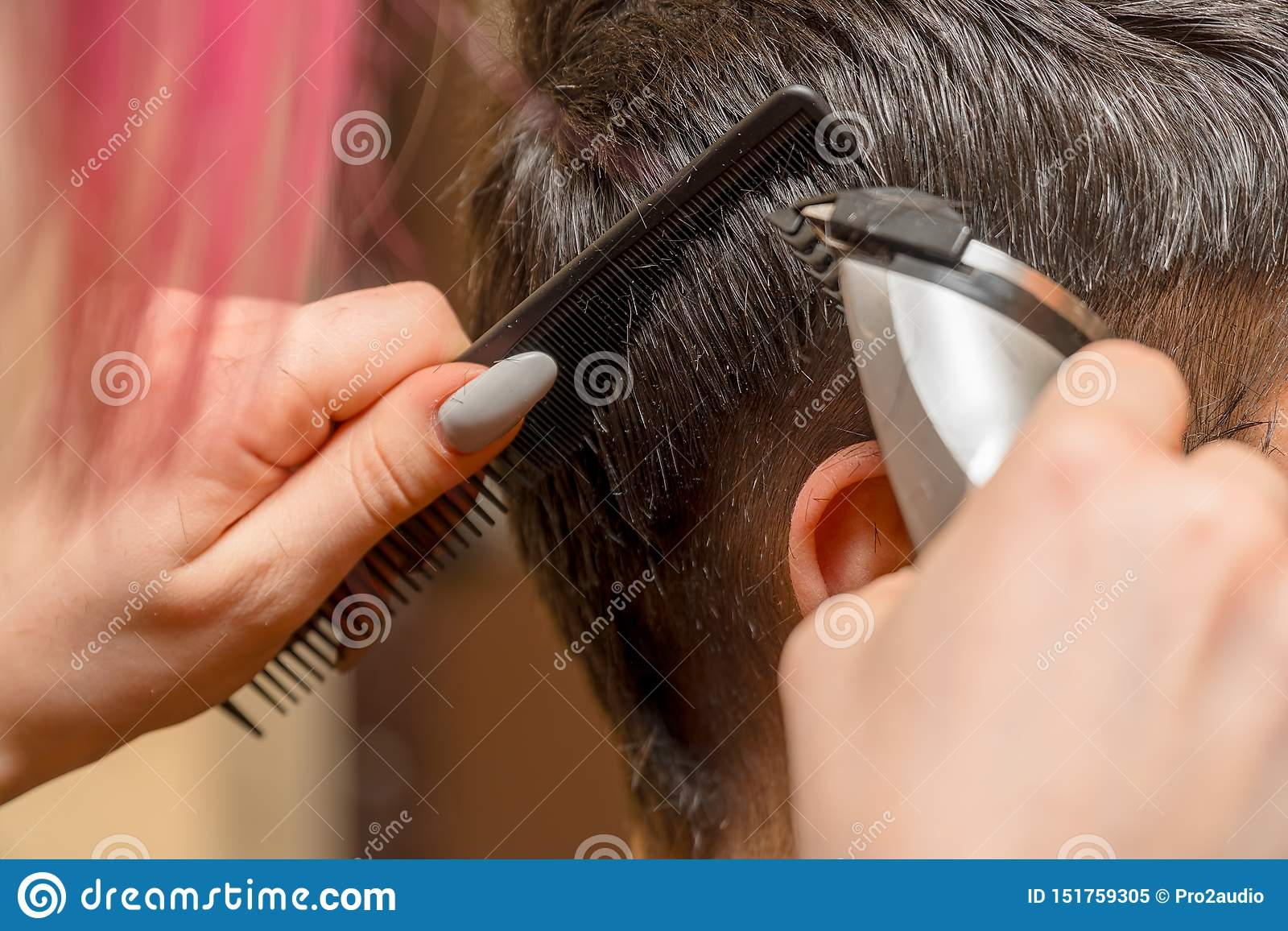 Woman Hairdresser cuts man s hair with electric clipper trimmer