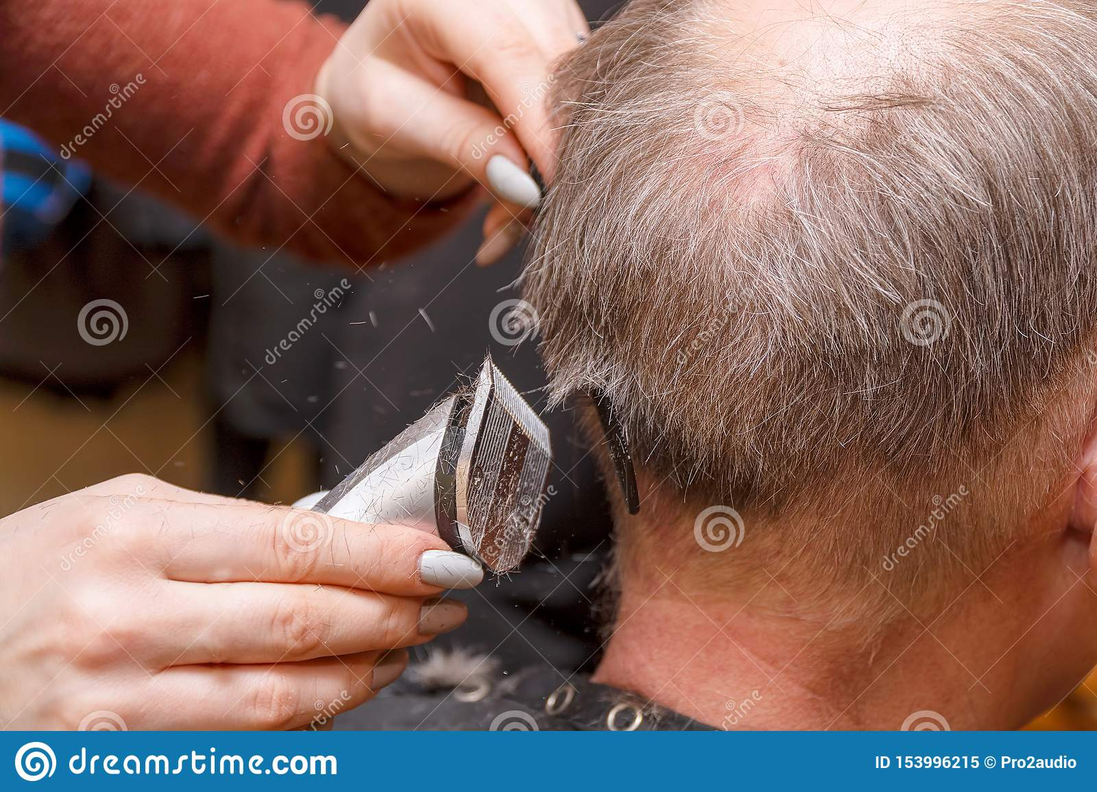 Woman Hairdresser cuts man`s hair with electric clipper trimmer