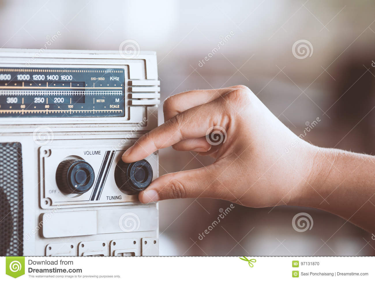 Woman hand adjusting the sound volume on retro radio cassette