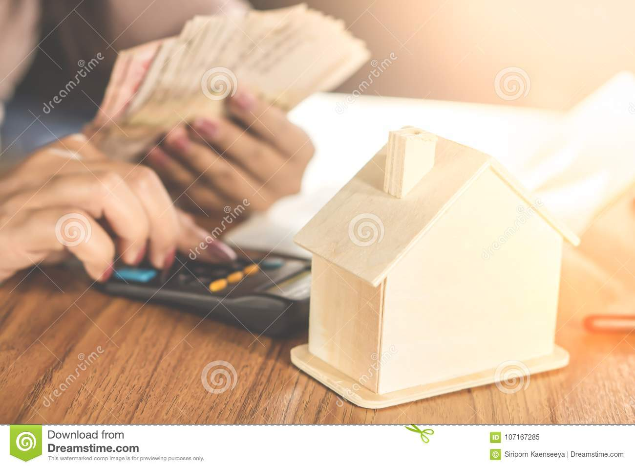 Woman hand calculating money with house model on wooden table planing to buy or rent home