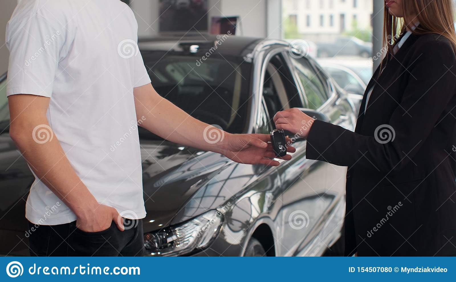 Woman hand gives a car keys to man hand in the car dealership close up. Unrecognized auto seller and a woman who bought