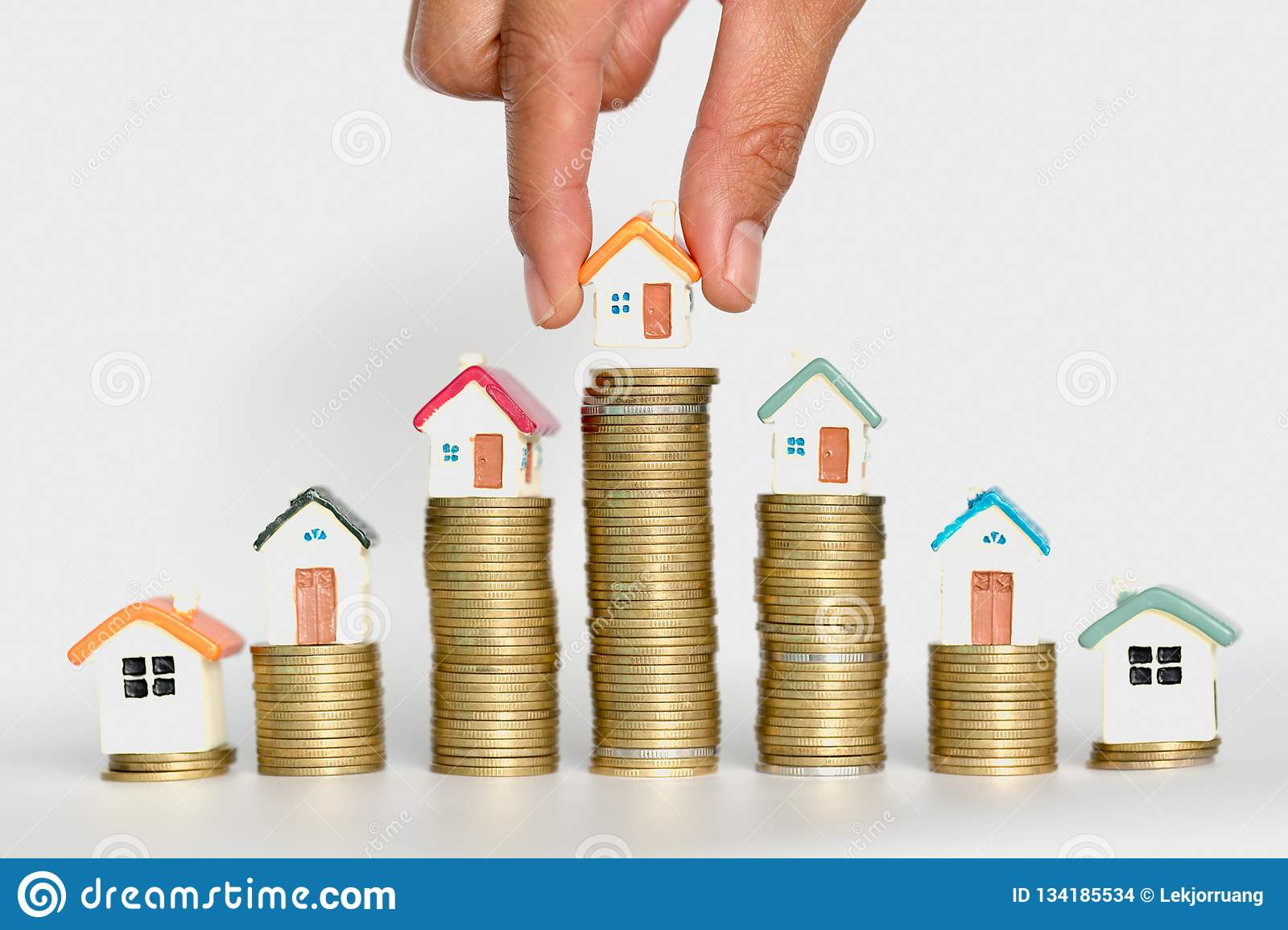 Woman hand hold a home model put on the stack coin with growing, Savings money for buy house and loan to business investment for