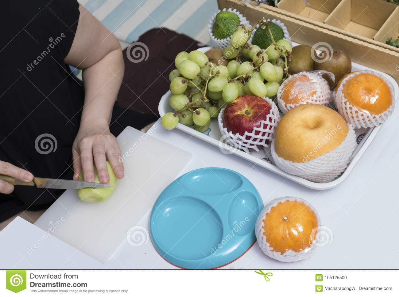 Woman hand hold knife cutting varity of fruit kiwi grapes apples