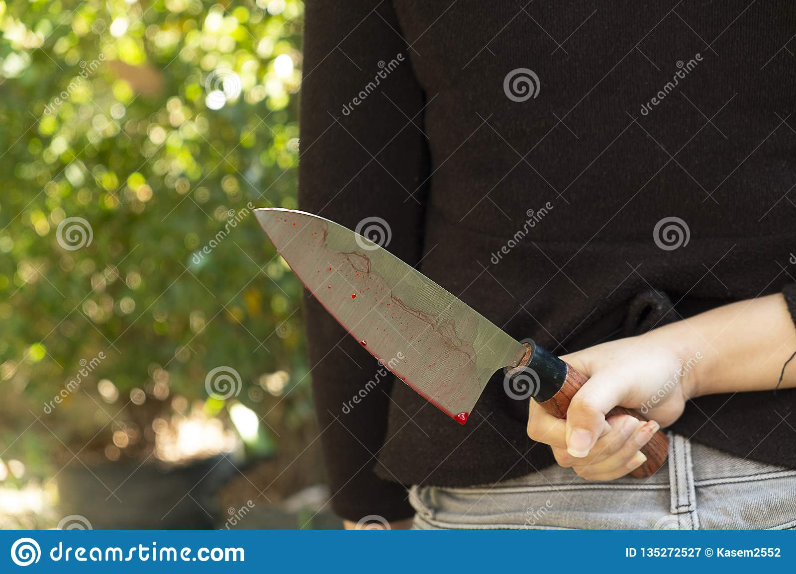 Woman hand holding a bloody knife on a black background,Social Violence Halloween Concept, photo of Serial diabolic killer, self