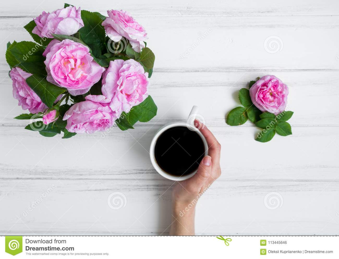 Woman hand holding cup of coffee, surrounded with rose flowers against white vintage wooden table. Flat lay, top view