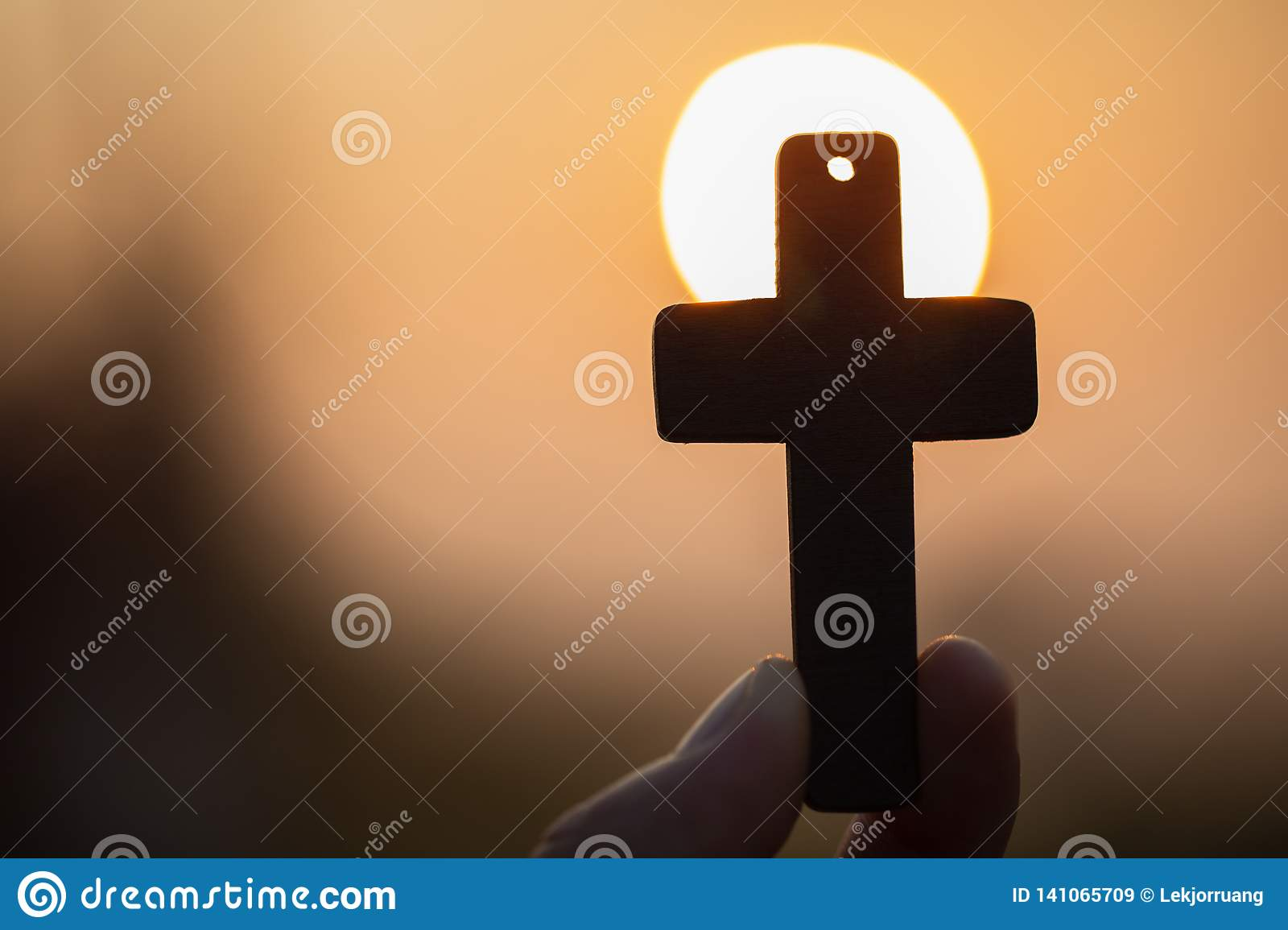 Woman hand holding holy lift of christian cross with light sunset background