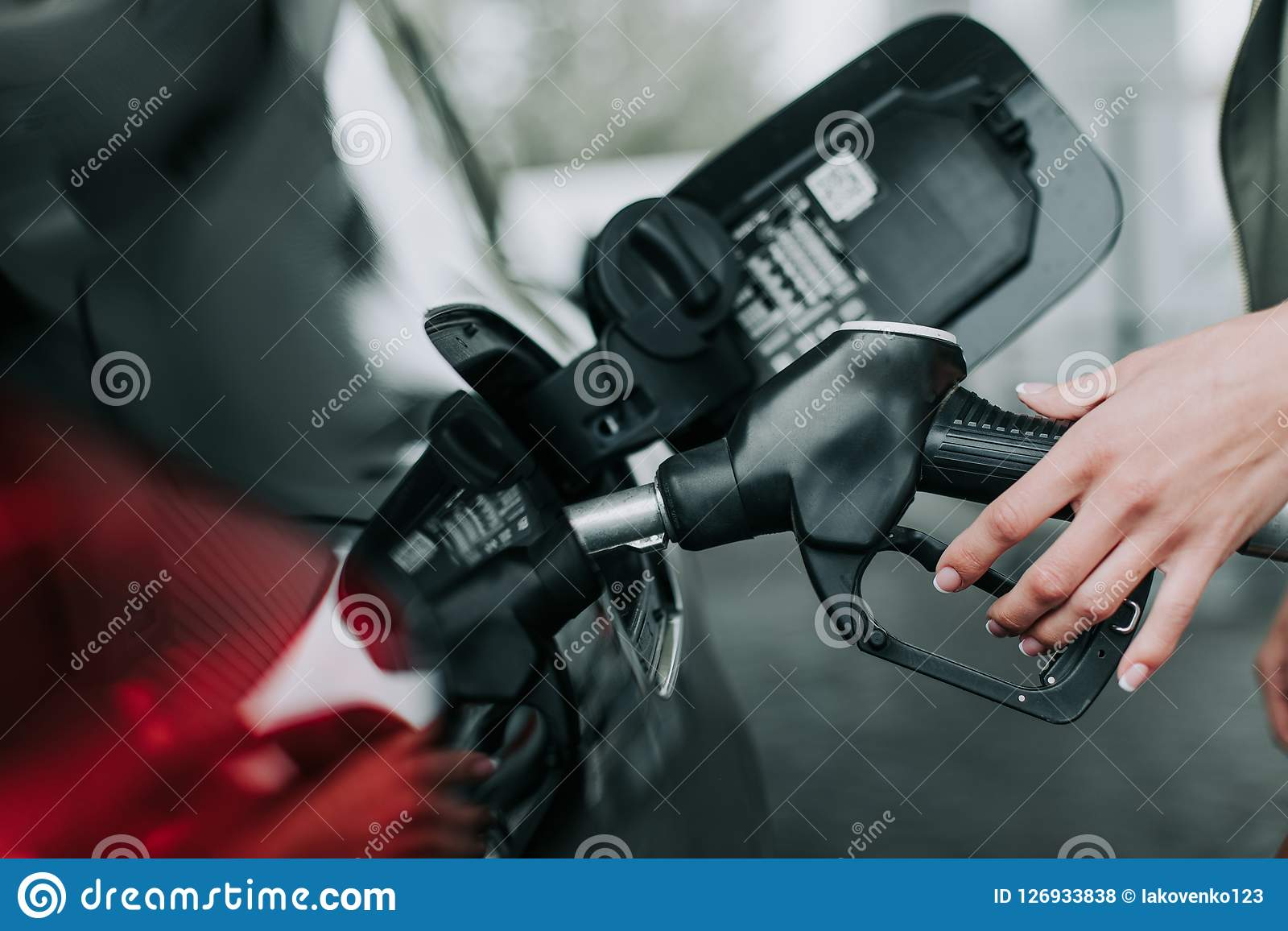 Woman hand holding petrol pump nozzle outdoor
