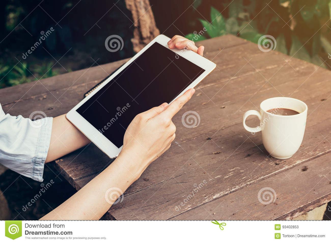 Woman hand holding tablet and blank screen display on wood table