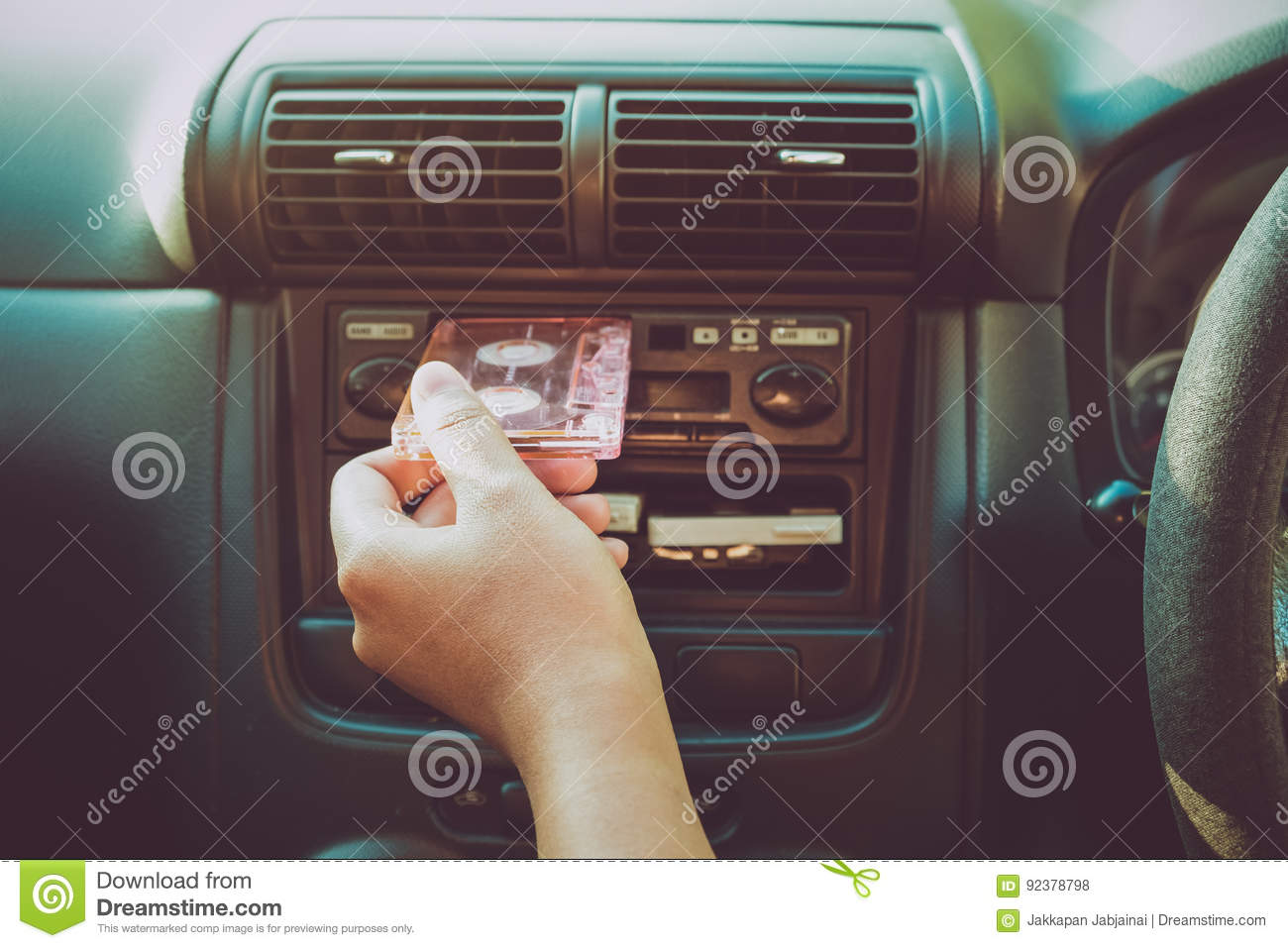 Woman hand holding tape cassette in car for driving listen music