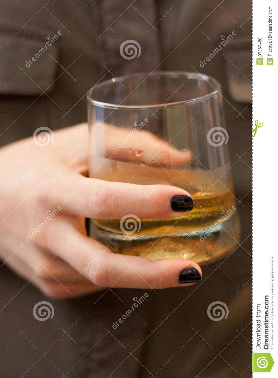 woman hand holding a whisky glass stock photo