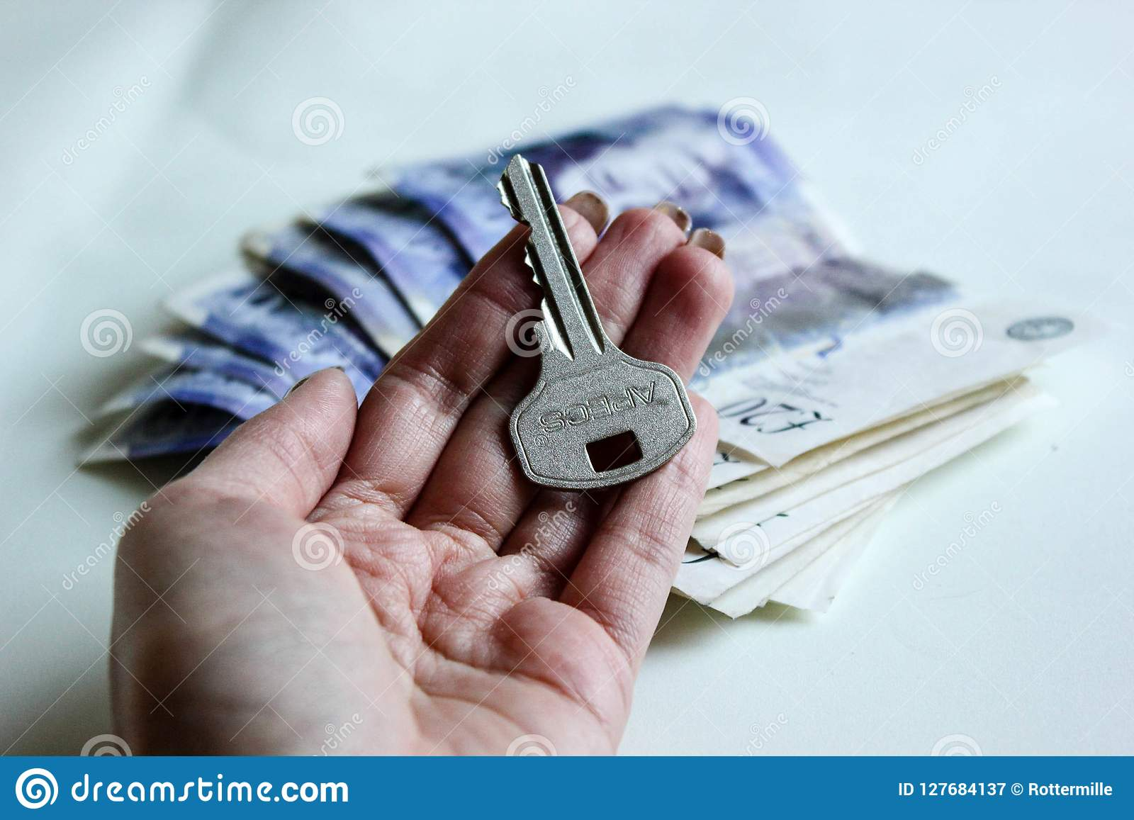 Woman hand with house key on a twenty pounds money roll background