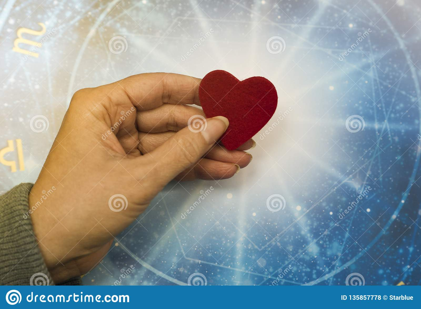 Woman hand keeping a red heart over blue horoscope like astrology, zodiac and love concept