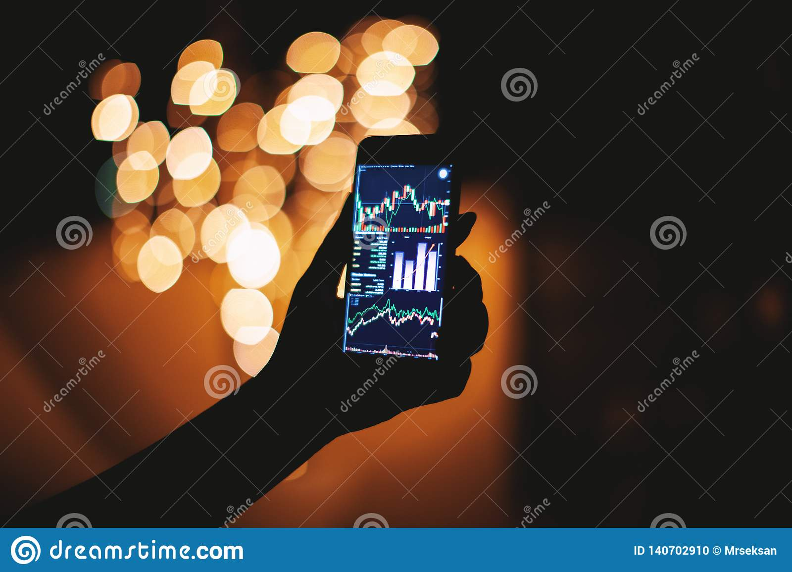 Woman hand with mobile phone with stock trading display in the dark with light bokeh background