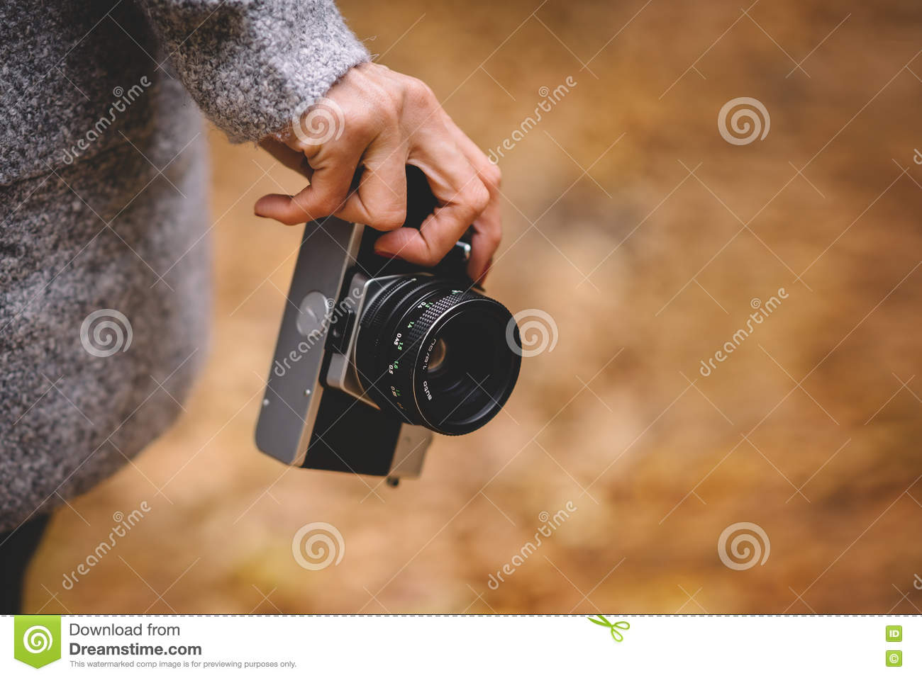 Woman hand with retro analog film camera. Concept for travel, wanderlust, outdoor adventure. Natural fall, defocused