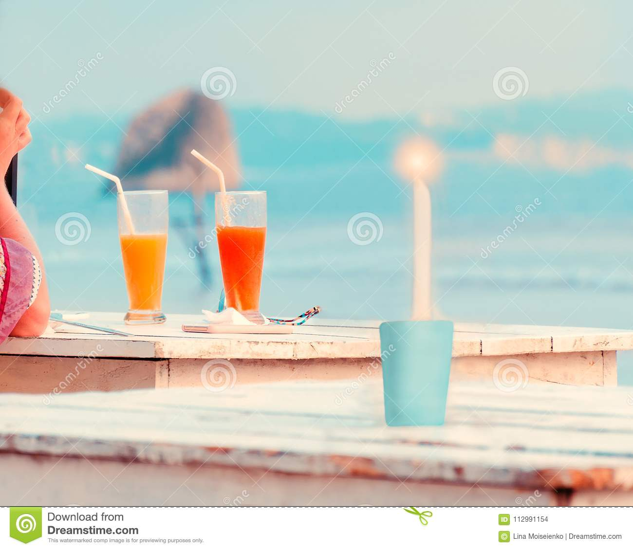 Woman hand , two glasses with fresh fruit juices, burning candle on wooden table in cafe on the beach.