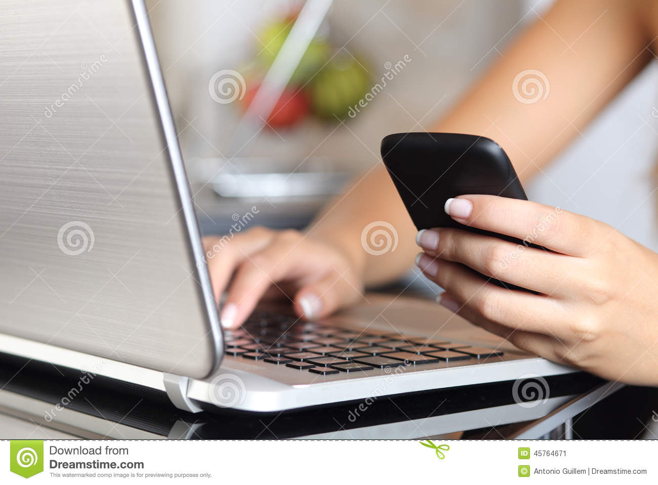 Woman hand using a smart phone and typing a laptop at home