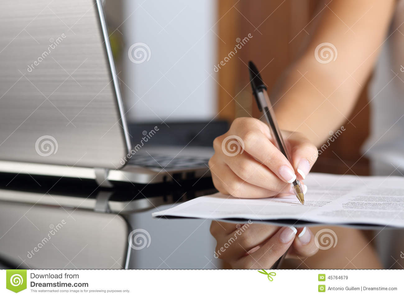 woman hand writing a contract with a laptop beside stock image