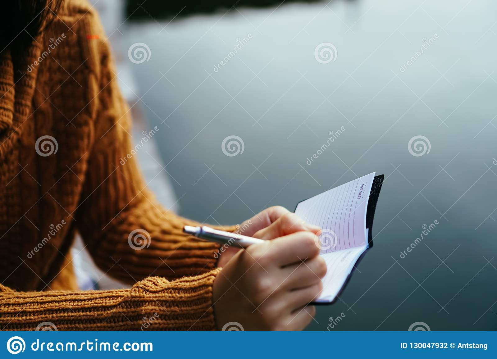 Woman hand writing down in small white memo notebook.