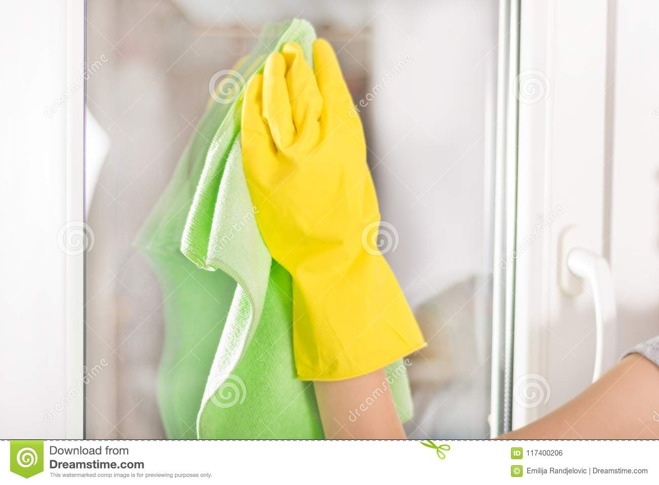 Woman hand with yellow protective glove and green rag cleaning window at home