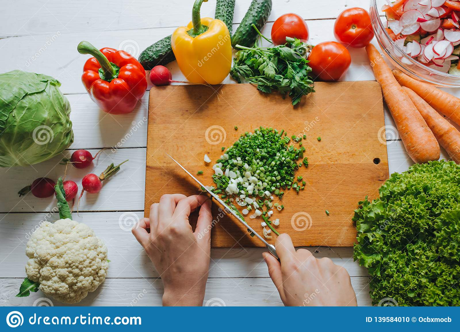 Woman hands cutting fresh green onion on wooden board overhead top view. White table background. Healthy cooking concept.