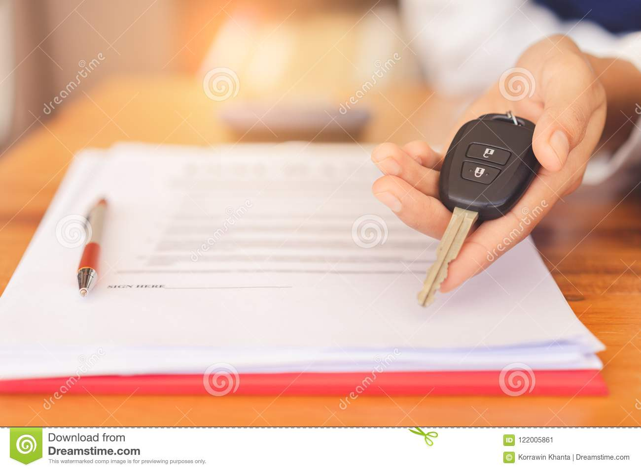 Woman hands giving a car remote key after signed contract agreement and successful deal.