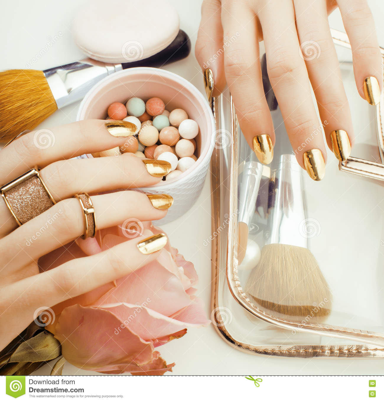 woman hands with golden manicure and many rings holding brushes