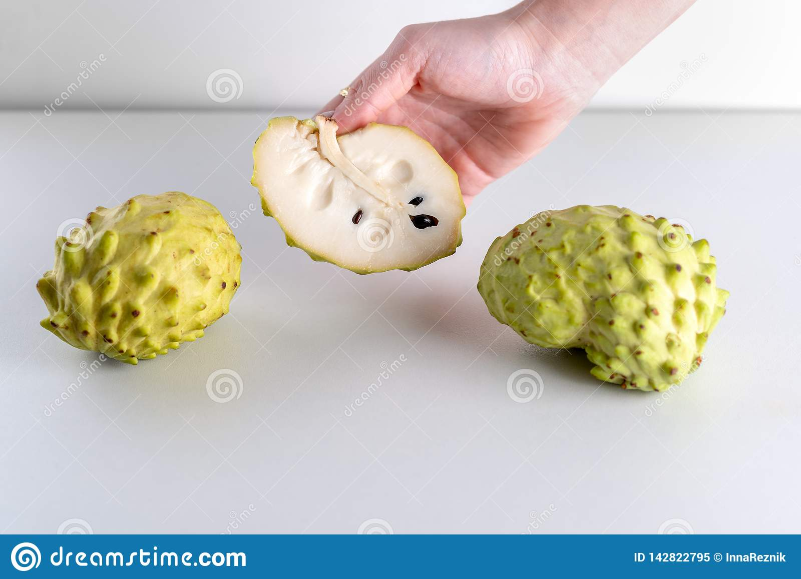 Woman Hands Holding Annona Fruit on White Background