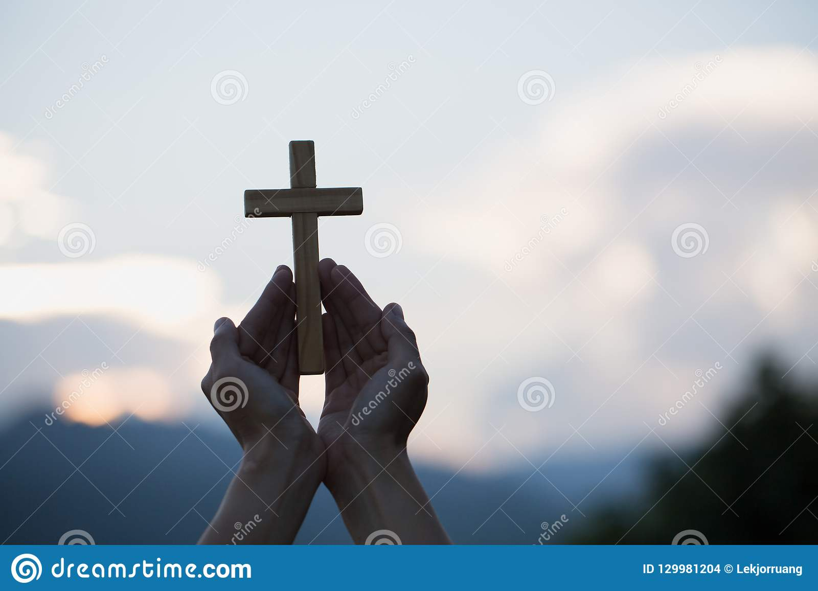 Woman hands holding holy lift of christian cross with light suns