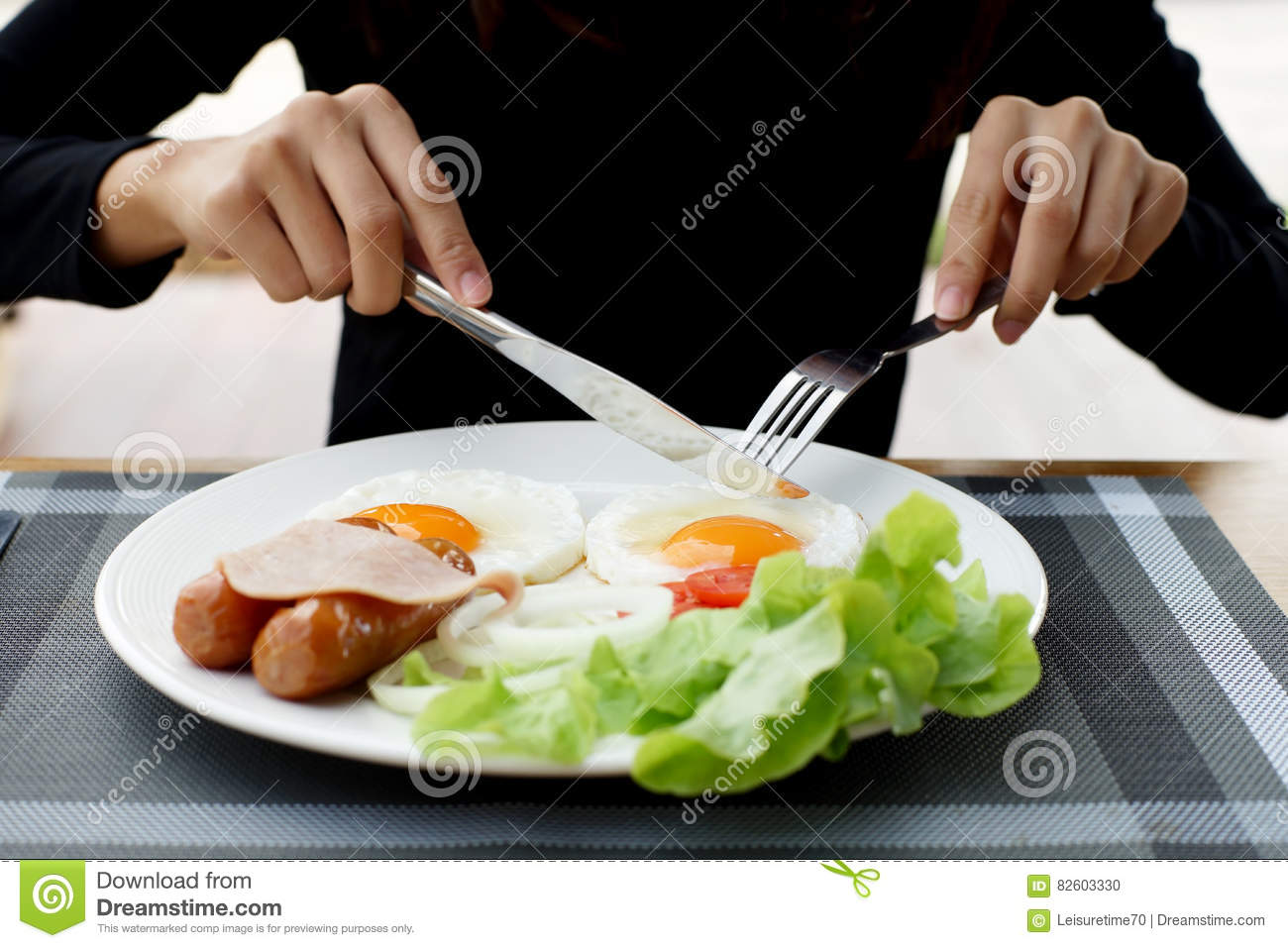 Woman hands holding knife and fork during eating breakfast