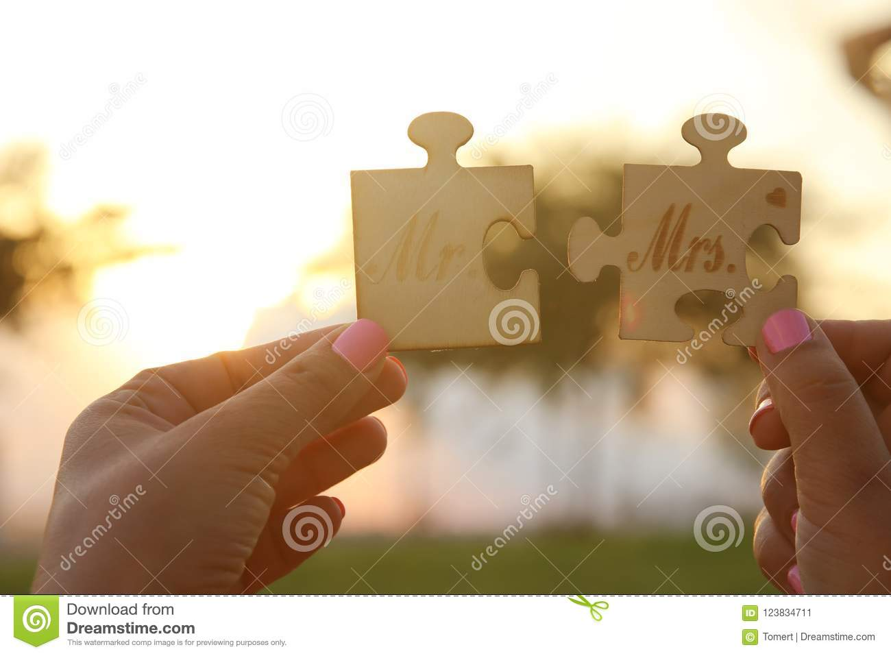 Woman hands holding Mr and Mrs sign during sunset time. harmony and wedding concept.