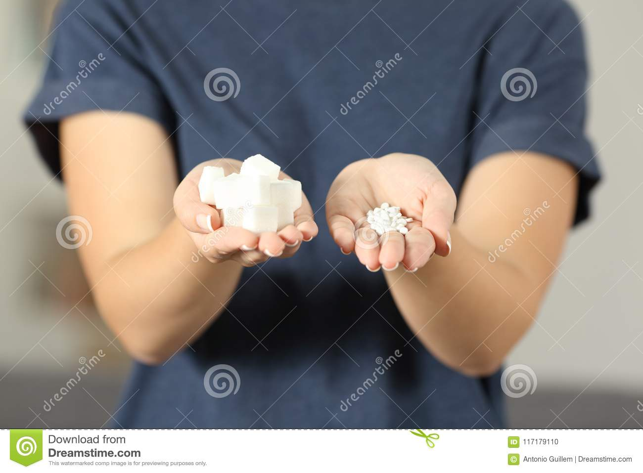Woman hands holding sugar cubes and saccharin pills