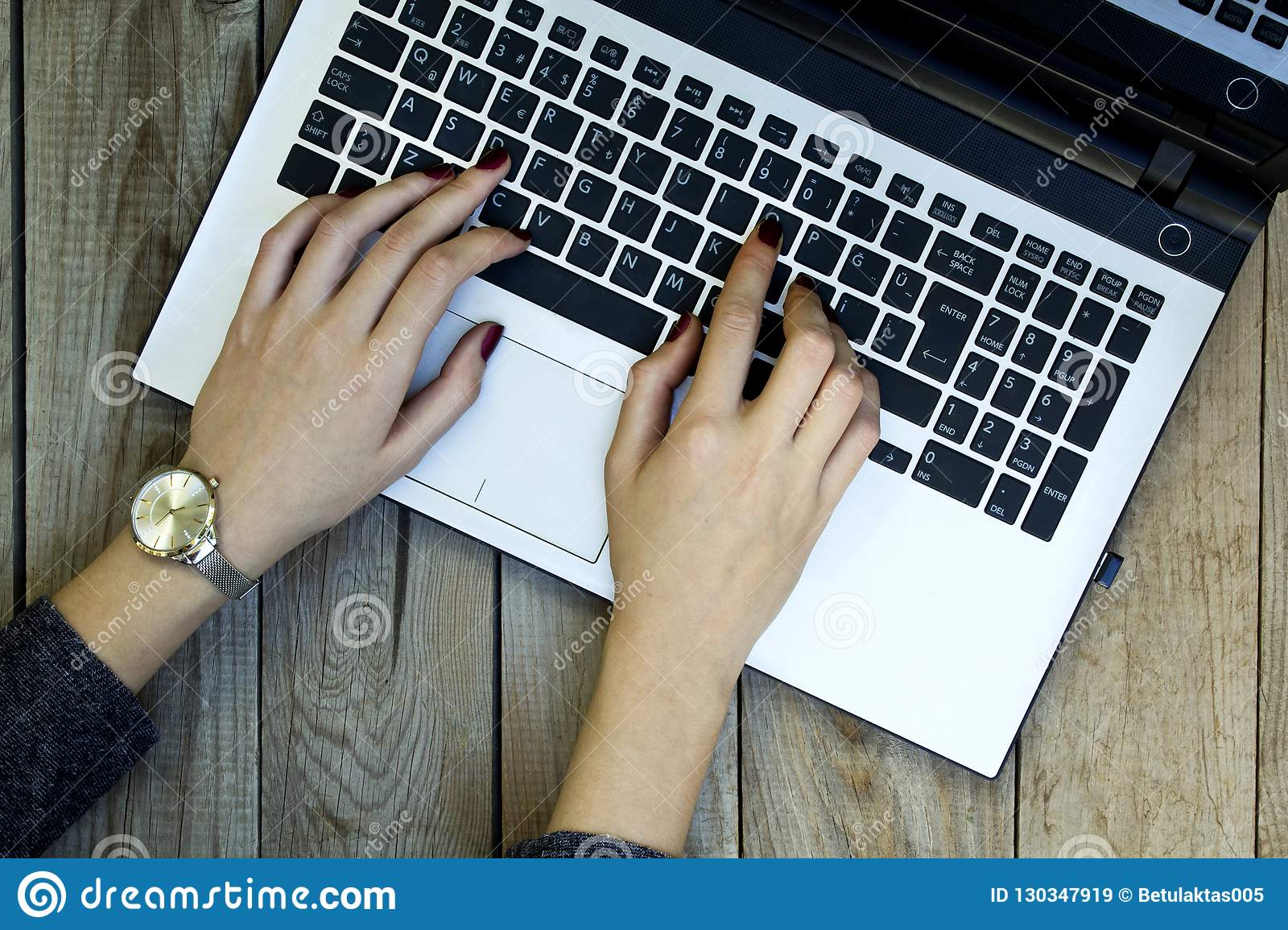 Woman hands using laptop on wooden background.