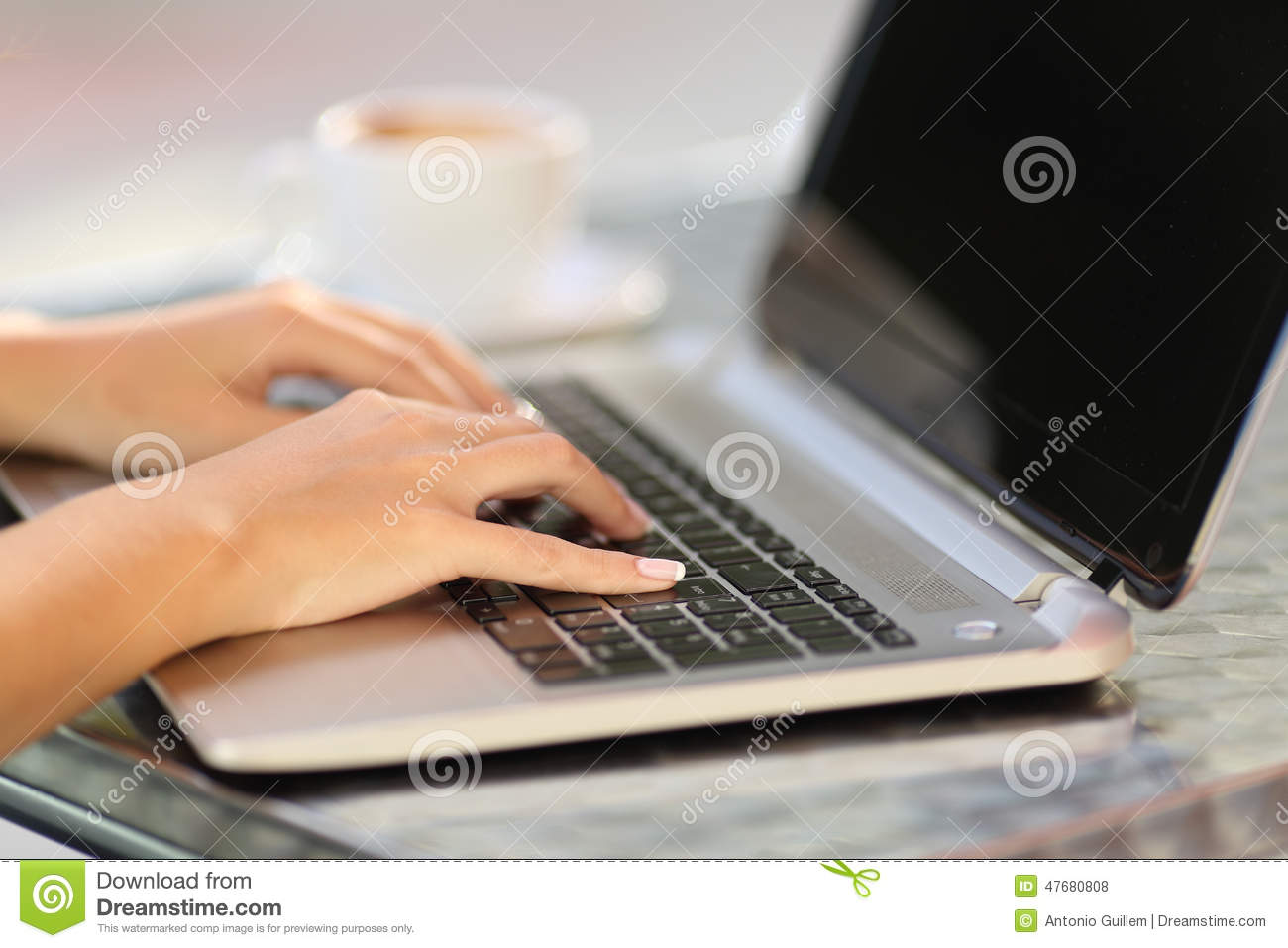 Woman hands working with a laptop in a coffee shop