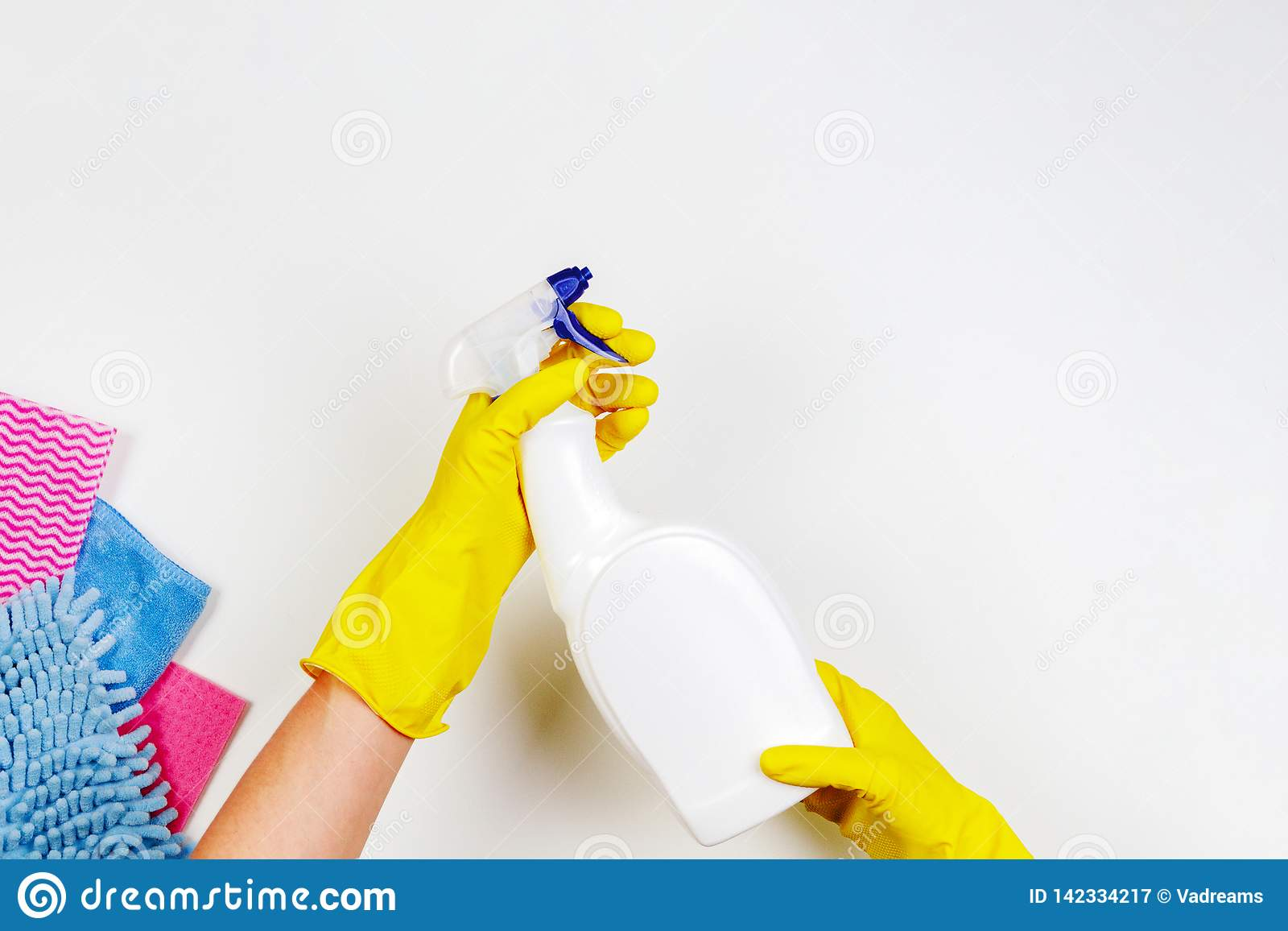 Woman hands in yellow rubber gloves click on white spray bottle with liquid detergent on white background. Housework