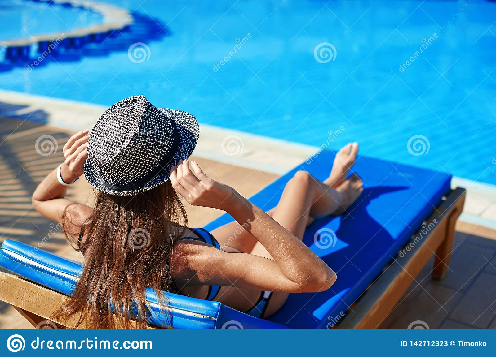 Woman in hat lying on a lounger near the swimming pool at the hotel, concept summer time to travel relax