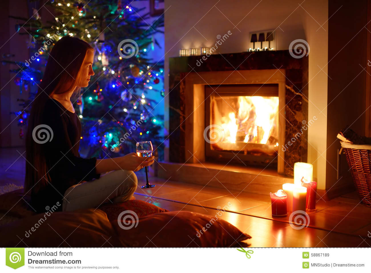 Woman Having A Drink By A Fireplace In A On Christmas Stock Photo