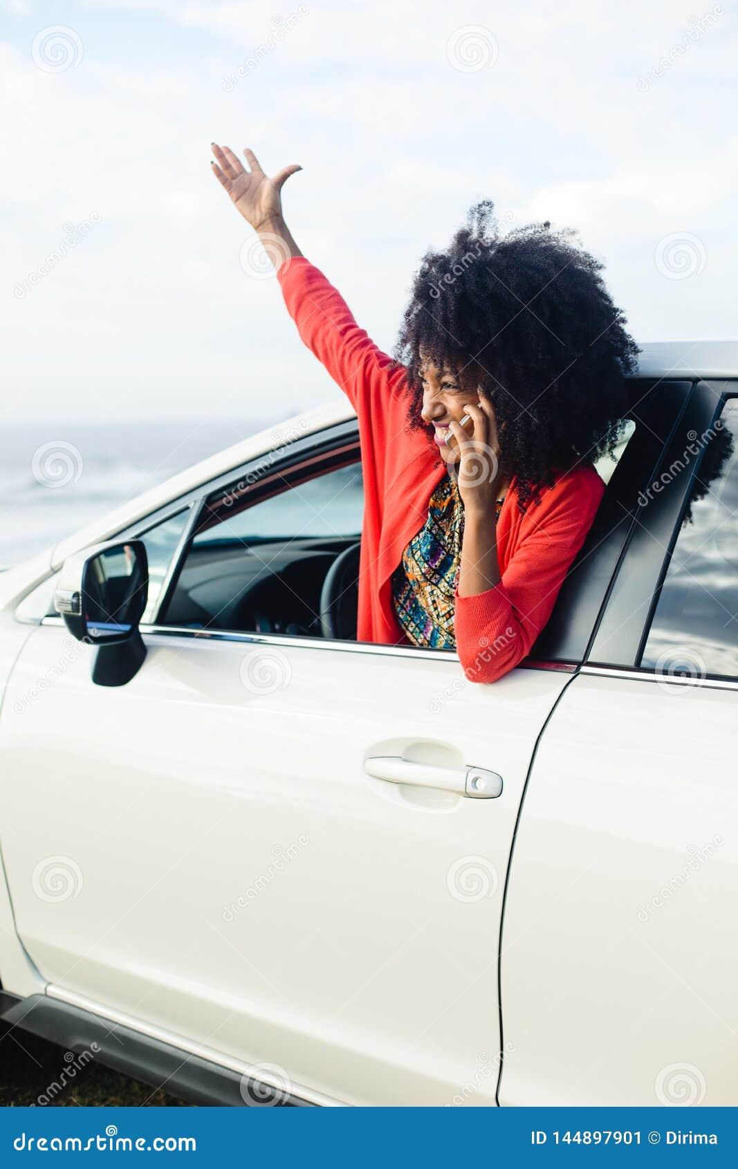 Woman having fun on car travel to the coast