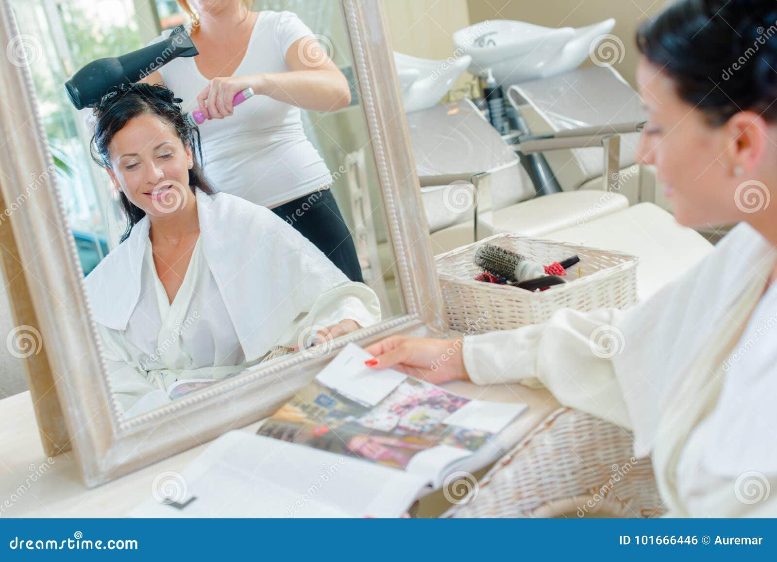 Woman having hair dried reading magazine