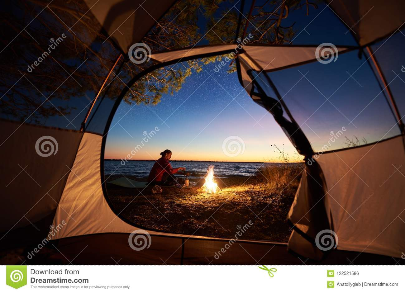 Woman having a rest at night camping near tourist tent, campfire on sea shore under starry sky