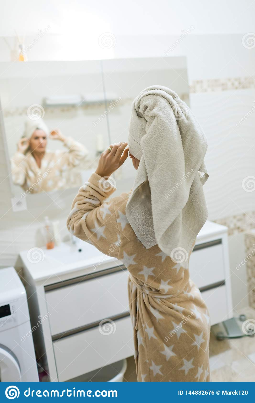 Woman having white towel on head after taking a shower
