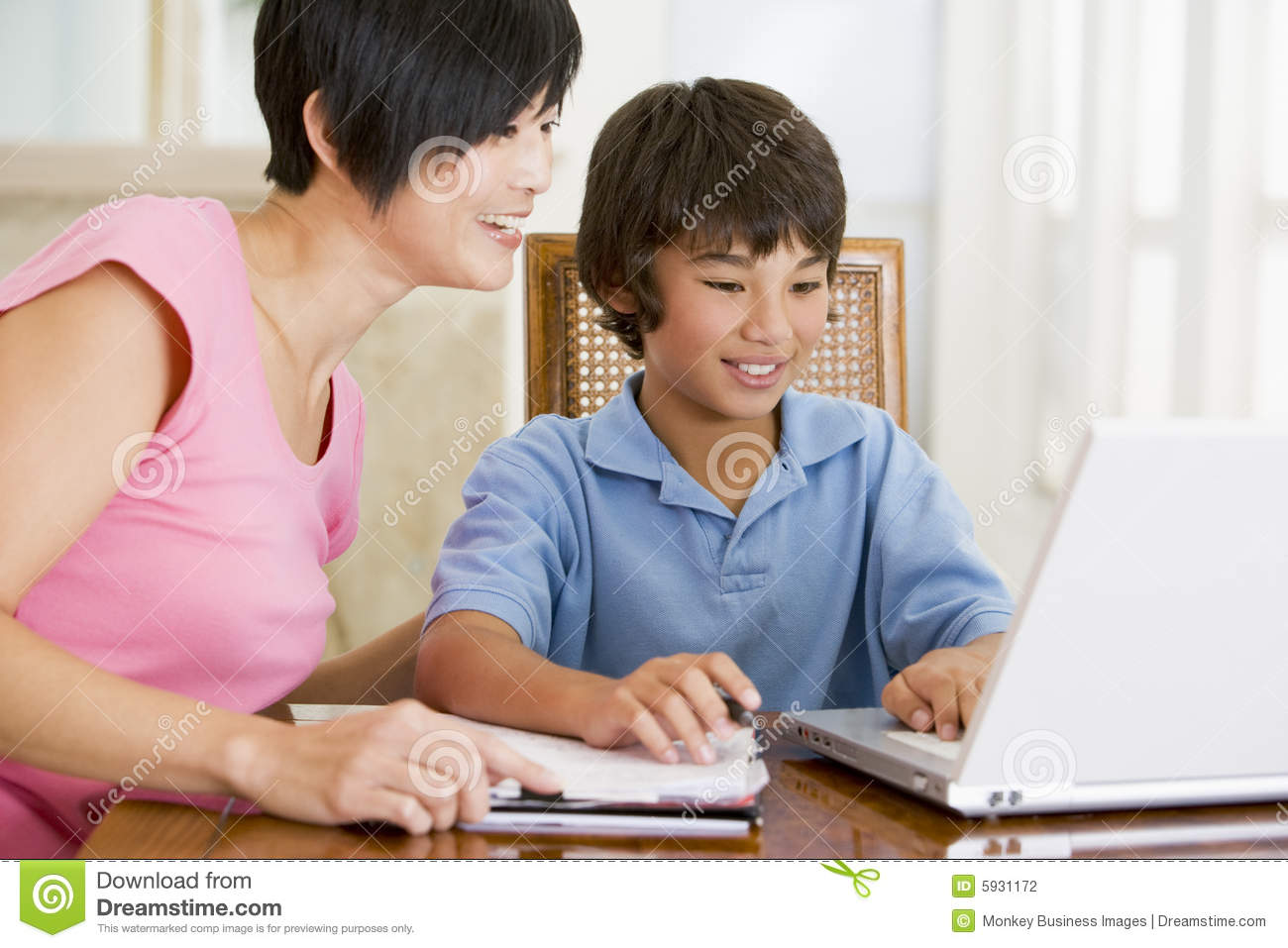 Woman helping boy with laptop doing homework