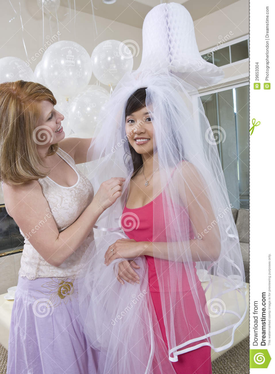Woman Helping Bride In Dressing Up At Hen Party Stock Photo