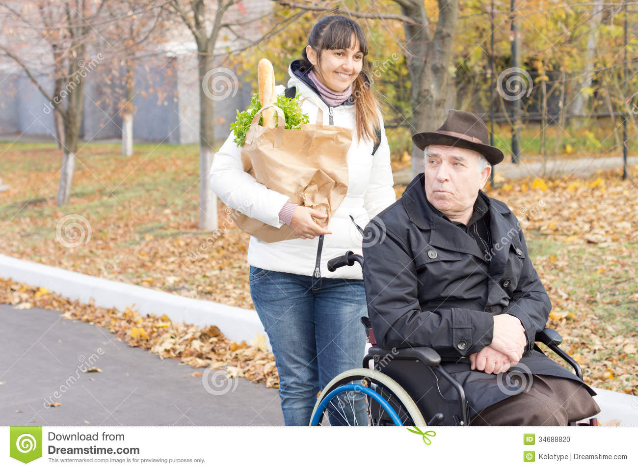 Smiling carer pushing an old man in a wheelchair stock photo image - Woman Helping A Disabled Man With Shopping Stock Photo