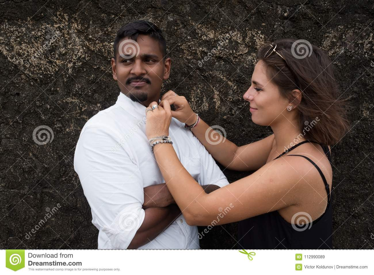 Woman helping her beloved man and fastening buttons on his shirt.