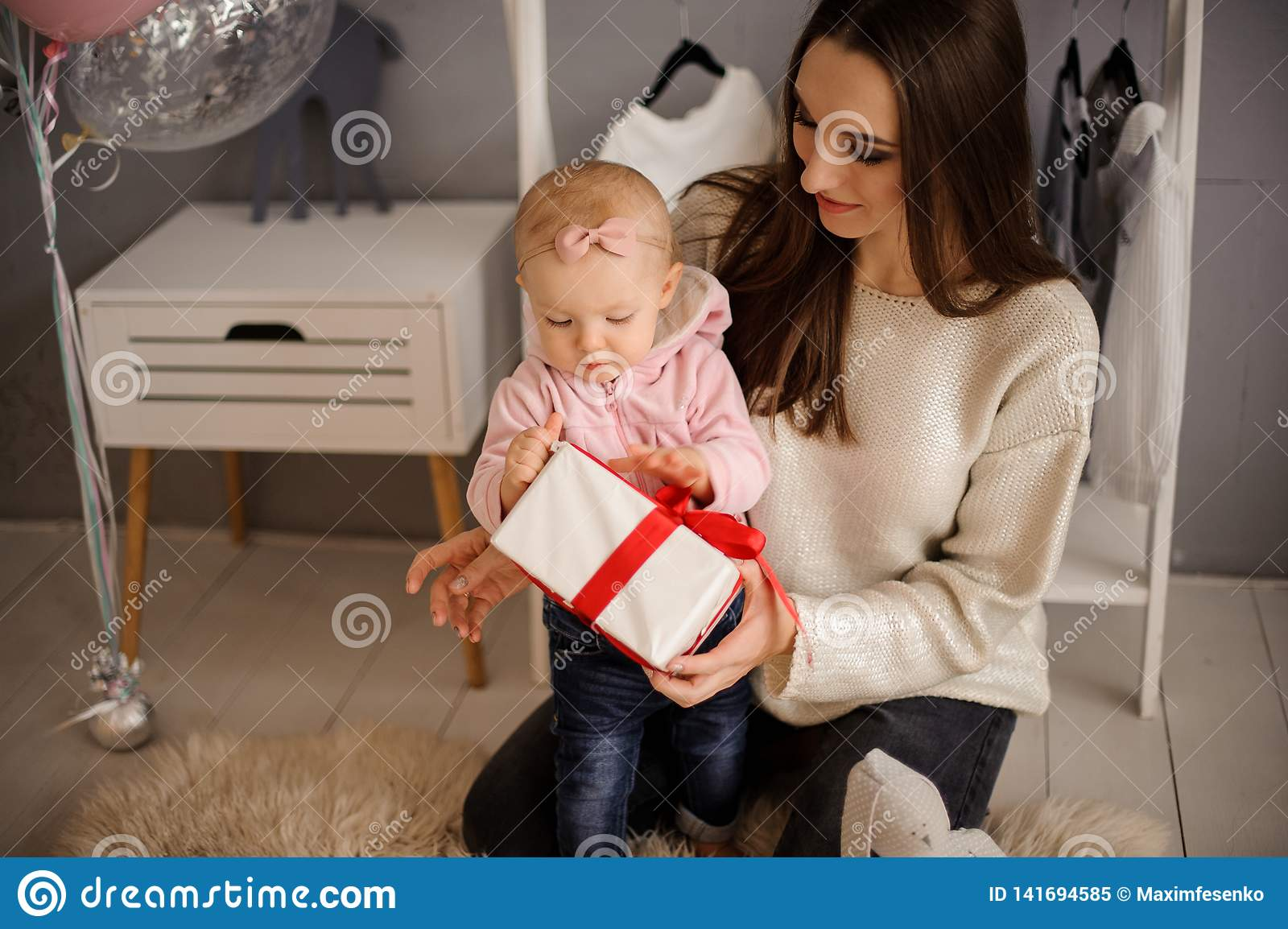 Woman and her cute little daughter holding a present