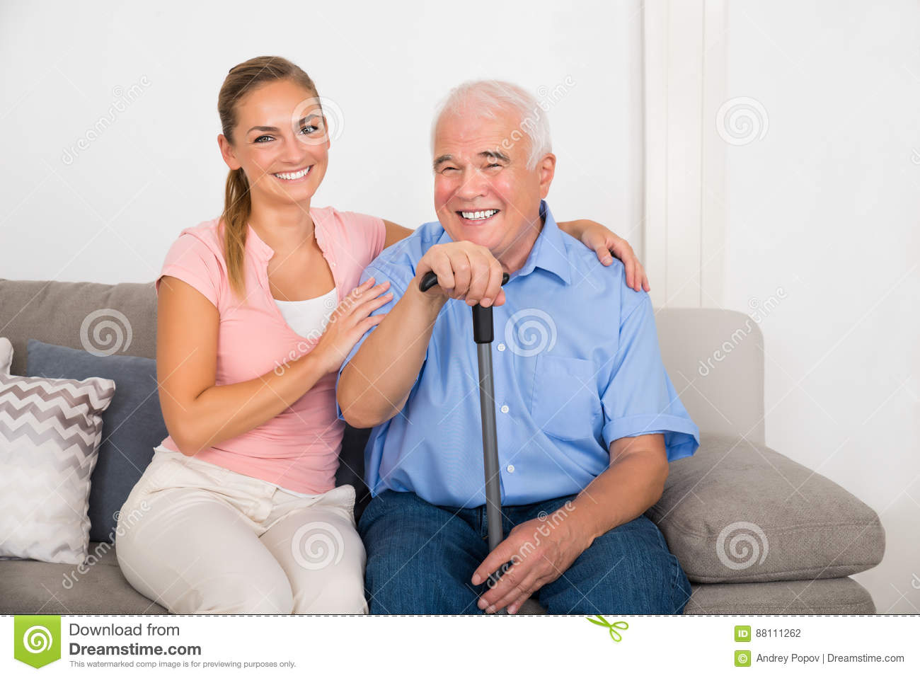 Woman With Her Disabled Father Sitting On Sofa