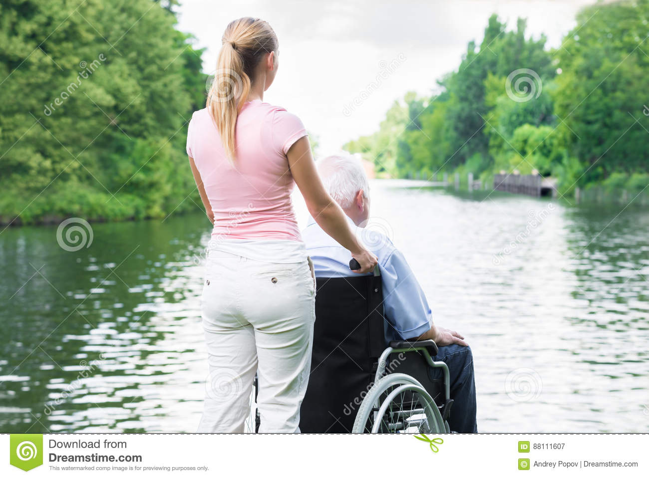 Woman With Her Disabled Father On Wheelchair Looking At Lake
