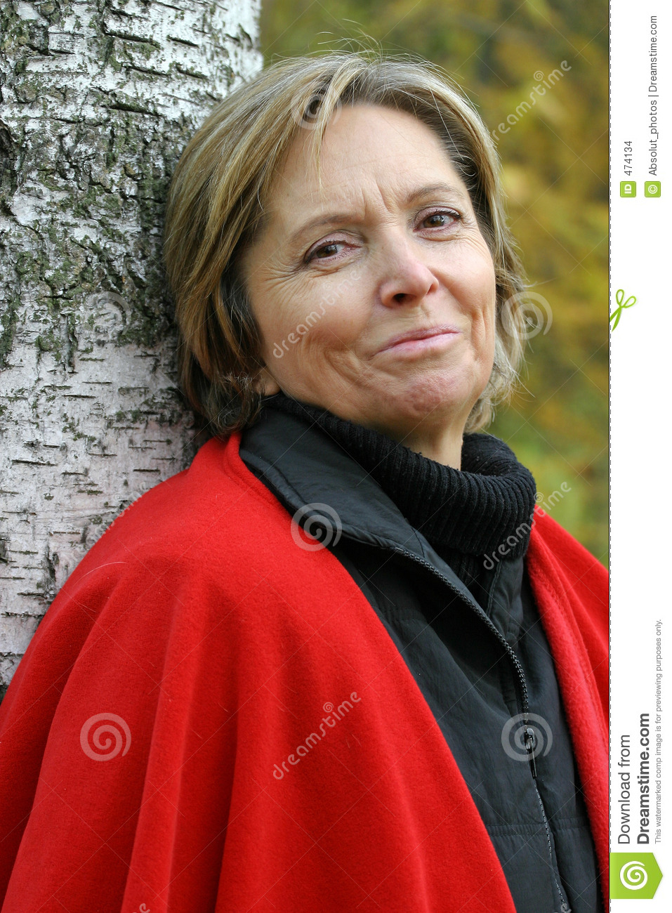 Woman in her fifties standing by the tree